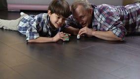 Papá y su niño que compiten en el lanzamiento de los pequeños coches del juguete, niñez feliz almacen de video