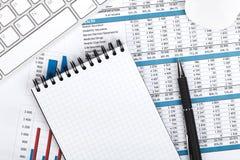 Papéis, computador e materiais de escritório financeiros Fotos de Stock Royalty Free