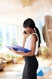 Papéis da leitura da mulher de negócios e fala no telefone imagens de stock royalty free