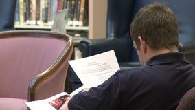 Papéis da leitura do homem em uma biblioteca video estoque