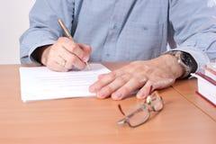 Papéis de assinatura do homem na tabela Fotografia de Stock