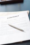 Papéis do contrato na mesa de madeira Fotos de Stock