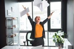 Papéis fêmeas alegres da carcaça no escritório fotos de stock