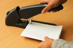 Papéis obrigatórios com o grampeador por ambas as mãos foto de stock royalty free