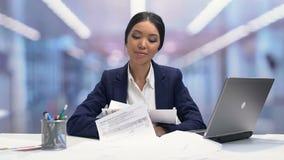 Papéis que caem em torno do empregado do sexo feminino calmo do escritório, tolerância alta para o esforço video estoque