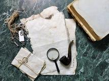 Papéis retros e livro na tabela de trabalho do detetive com ferramentas Fotografia de Stock Royalty Free