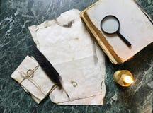 Papéis retros e livro na tabela de trabalho do detetive com ferramentas Fotos de Stock