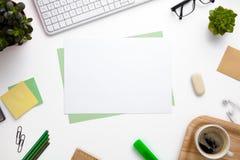 Papéis vazios cercados com materiais de escritório na mesa branca Imagem de Stock