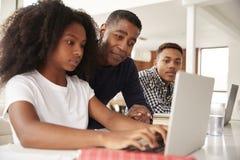Pap? afroamericano envejecido medio que ayuda a sus ni?os adolescentes con la preparaci?n, ?ngulo bajo, cierre para arriba fotos de archivo