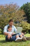 Papà allegro e figlio con un computer portatile Immagine Stock