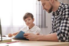 Pap? che aiuta suo figlio con l'assegnazione di scuola immagini stock libere da diritti