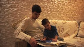 Pap? con capelli neri in un maglione bianco ed in un piccolo figlio in un blu, a strisce, sguardo all'enciclopedia, sedentesi su  stock footage