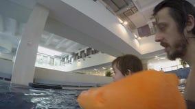 Pap? e piccolo nuoto del figlio nello stagno dell'interno video d archivio