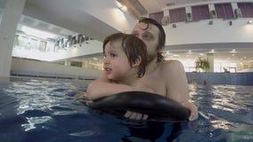 Pap? e piccolo nuoto del figlio nello stagno dell'interno stock footage
