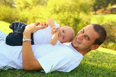 Papà felice e bambino che pongono sull'erba esterna Fotografia Stock Libera da Diritti