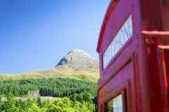 The Pap of Glencoe With Telephone Box. The Pap of Glencoe mountain in the Scottish Highlands named Sgurr na Cìche in Scottish gaelic with a juxtaposition out of Royalty Free Stock Photos