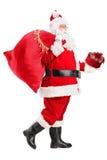 Papá Noel que recorre con el bolso y el regalo en sus manos Imágenes de archivo libres de regalías