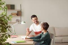 Pap? que ayuda a su hijo con la asignaci?n de escuela fotografía de archivo libre de regalías