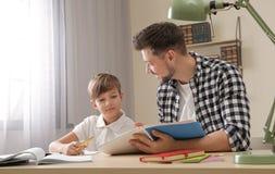 Pap? que ayuda a su hijo con la asignaci?n de escuela imágenes de archivo libres de regalías
