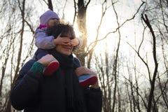 Pap? que lleva a su beb? en sus hombros en bosque imagenes de archivo