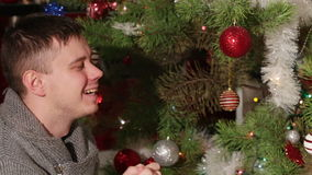 Pap throws up baby near Christmas tree stock video footage