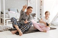 Papa émotif et sa fille jouant des jeux vidéo Photo libre de droits