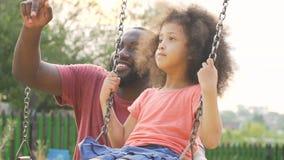 Papa affectueux balançant son enfant dans la cour et se dirigeant vers le haut, valeurs familiales lent-MOIS banque de vidéos