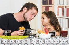 Papa affectueux d'amusement prenant le petit déjeuner avec petit image libre de droits