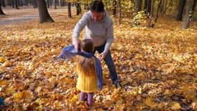 Papa affectueux et s'inquiétant jouant avec sa fille en automne banque de vidéos