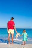 Papa avec la petite fille tenant le jouet de lapin sur la plage des Caraïbes Photographie stock libre de droits