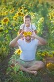 Papa avec le fils étreignant dans un domaine des tournesols Étreinte de fils son père dans un domaine des tournesols images stock
