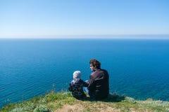 Papa avec le fils dans le bord de montagnes Photographie stock