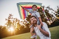 Papa avec le fils jouant avec le cerf-volant photo stock