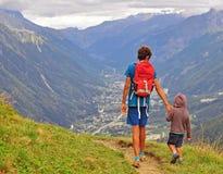 Papa avec le fils marchant en montagnes Photographie stock libre de droits