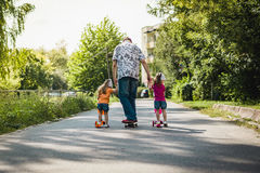 Papa avec ses filles sur une planche à roulettes et un scooter Photos stock