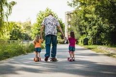 Papa avec ses filles sur une planche à roulettes et un scooter Photographie stock