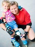 Papa avec son descendant sur les patins photo stock