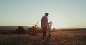 Papa avec son garçon trois années, au coucher du soleil au milieu du champ jouant avec une petite raquette pour la table de tenni banque de vidéos