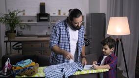 Papa bezig met huishoudelijk werk die zoon met thuiswerk helpen stock footage