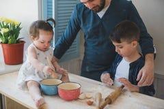 Papa cultivé de photo avec son petits fils et fille faisant cuire au four ensemble photos libres de droits