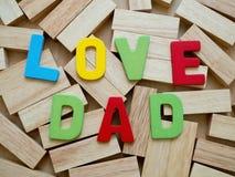 Papa d'amour Father& heureux x27 ; célébrations de jour de s Aimez le mot de papa de coloré du bois sur le bloc en bois à l'arriè Images stock