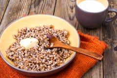 Papa de aveia delicioso do trigo mourisco com manteiga e leite Imagens de Stock