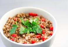 Papa de aveia delicioso do trigo mourisco com pimenta vermelha e ramo doces desbastados da salsa na parte superior Imagem de Stock