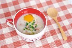 Papa de aveia do arroz com o ovo na bacia bonito Imagens de Stock Royalty Free