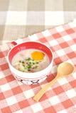 Papa de aveia do arroz com o ovo na bacia bonito Imagem de Stock Royalty Free