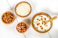 Papa de aveia do leite do arroz com porcas e passas em umas bacias de madeira em um wh Fotos de Stock
