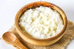 Papa de aveia do leite do arroz com porcas e passas em umas bacias de madeira em uma tabela de madeira branca Fotos de Stock
