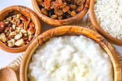 Papa de aveia do leite do arroz com porcas e passas em umas bacias de madeira em uma tabela de madeira branca Imagens de Stock