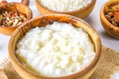 Papa de aveia do leite do arroz com porcas e passas em umas bacias de madeira em uma tabela de madeira branca Imagem de Stock Royalty Free