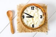 Papa de aveia do leite do arroz com porcas e passas em umas bacias de madeira em uma tabela de madeira branca O conceito de um ca Fotografia de Stock Royalty Free